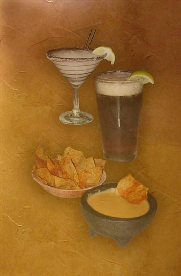 Two glasses of cocktails, a bowl of nachos and a bowl of dipping sauce