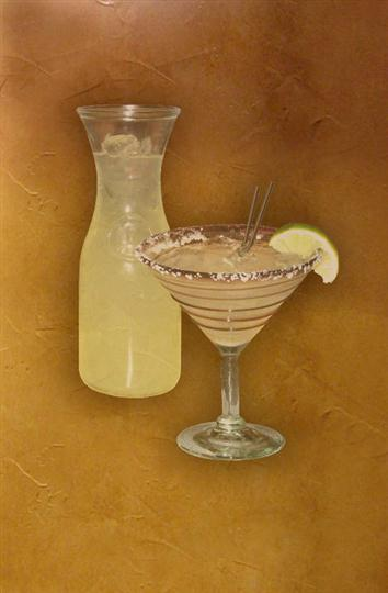 A glass and a carafe of margarita