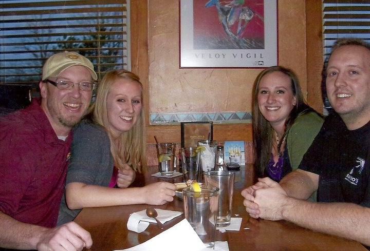 Two couples sitting at a restaurant's table smiling for the photo