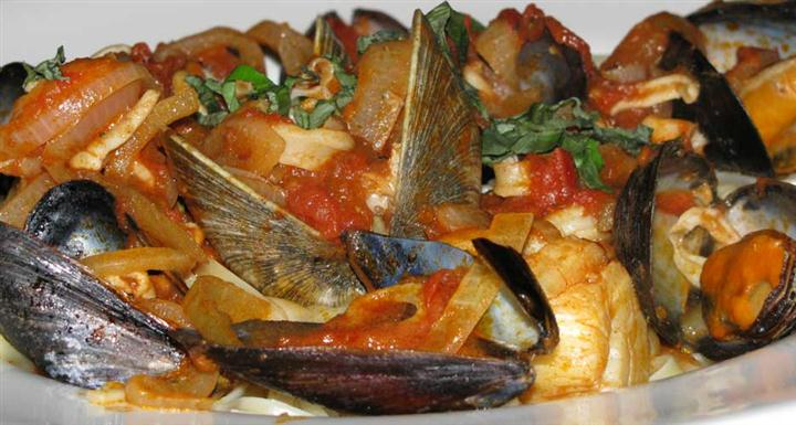 a dish with muscles and other seafood topped with a tomato sauce