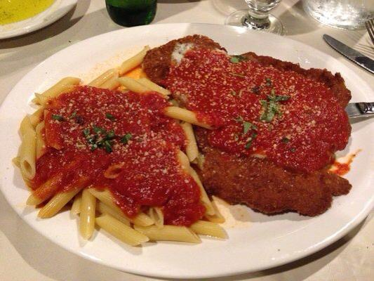 a plate of chicken parmigiana  and penne topped with marinara sauce