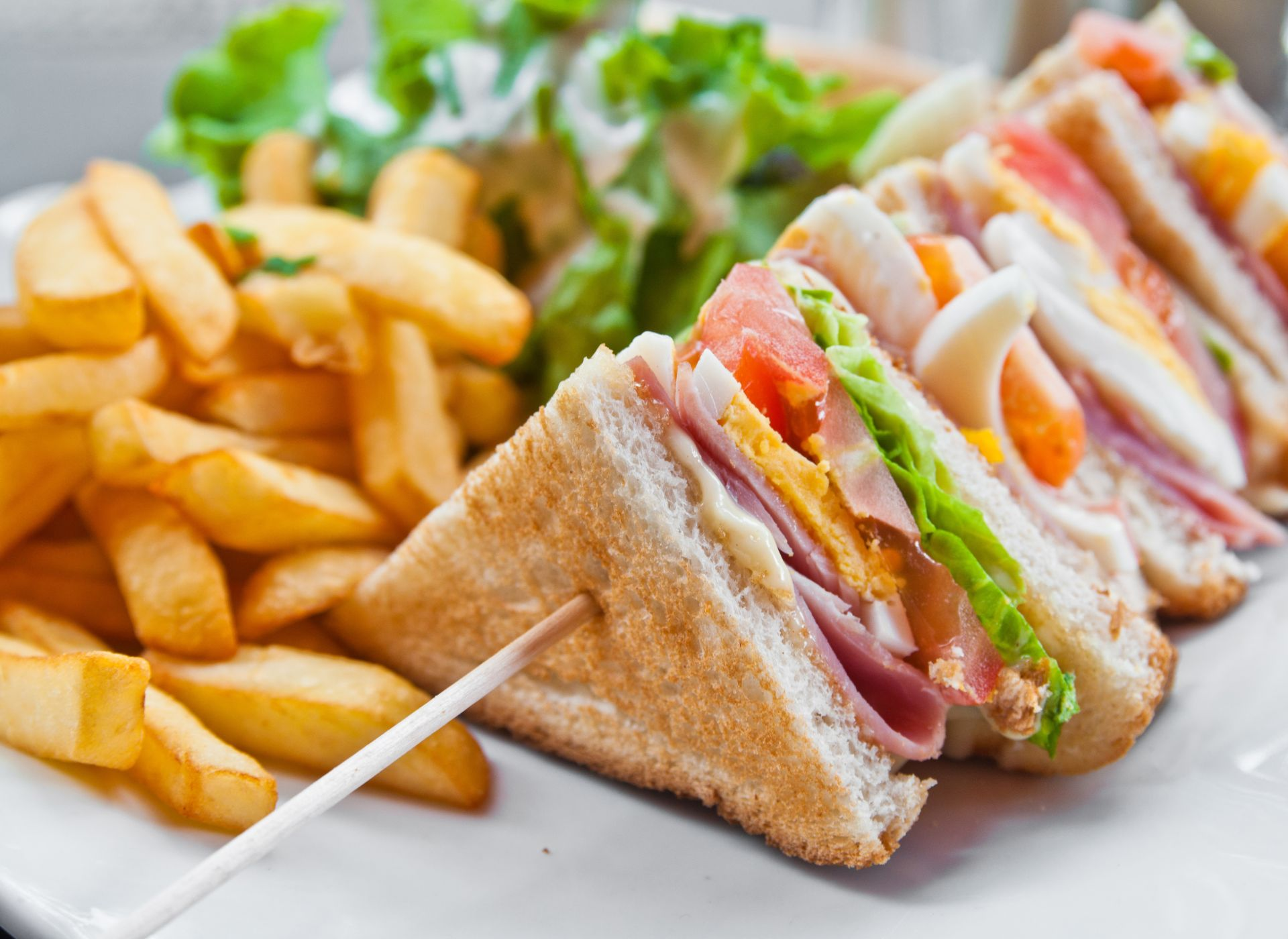 Triple decker club sandwich with ham, hard boiled egg, lettuce and tomato on a plate with French fries