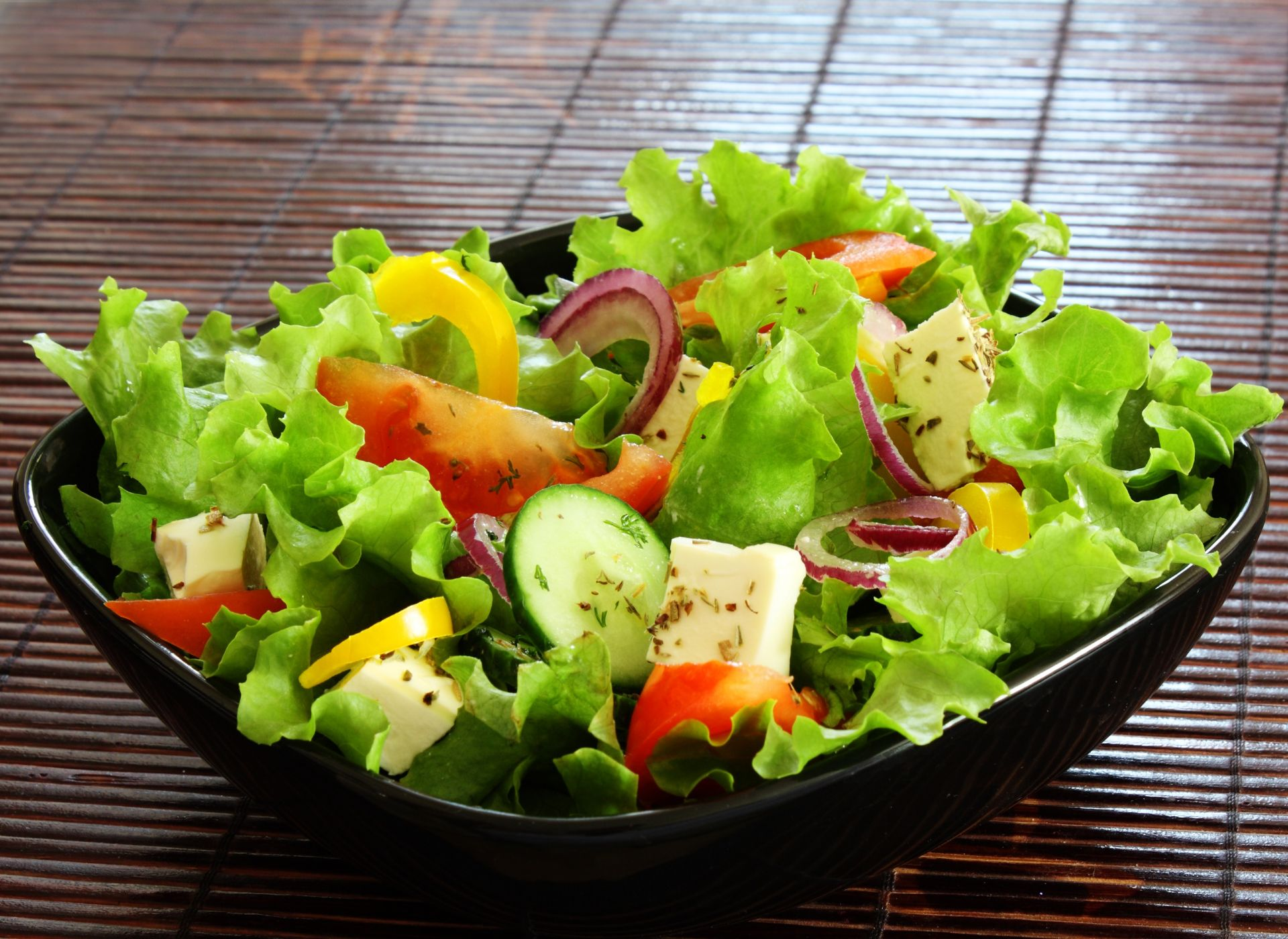 Garden salad with tomatoes, cucumbers, red onion and cheese in a bowl