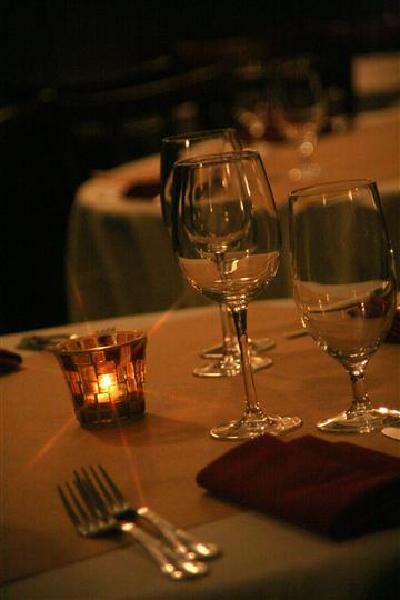 Closeup of table with dim lighting and a candle lit.