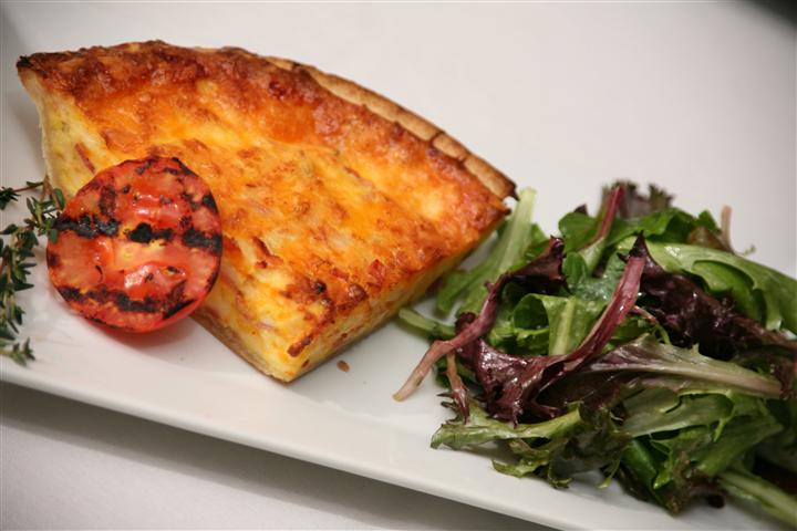Baked deep dish pasta with a grilled tomato and a small greens salad on the side.