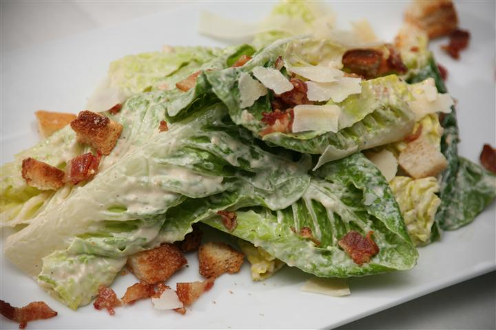 Romaine lettuce leaves with bacon bits, caesar dressing, croutons and shaved parmesan.