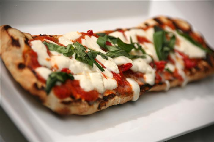 Grilled flatbread with fresh mozzarella, roasted tomatoes, basil, field greens