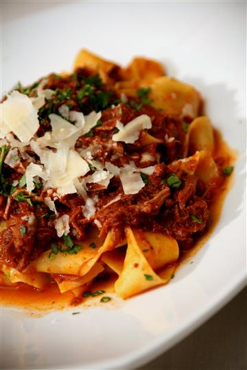 Pasta with a meat sauce and shaved Parmesan cheese.