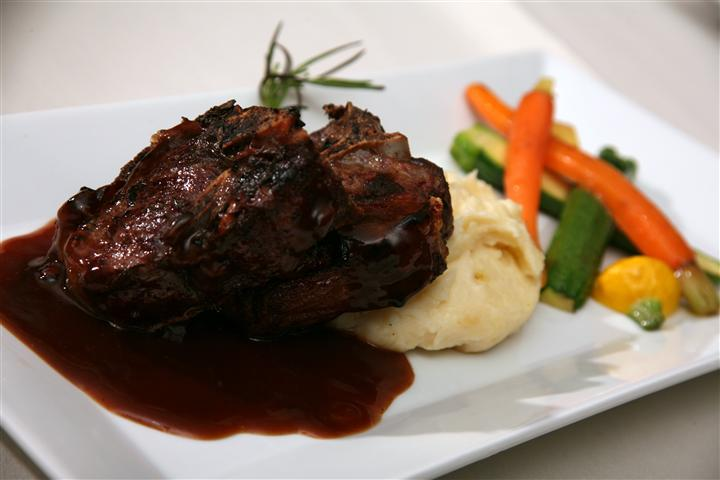 Steaks over mashed potatoes with vegetables