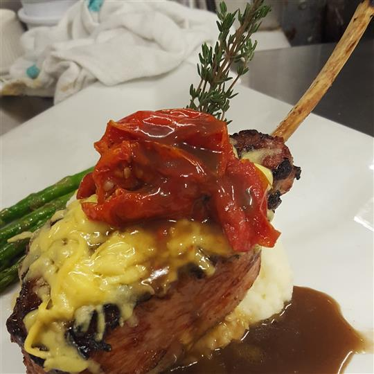 Lamb topped with cheese and roasted red pepper with a side of asparagus.