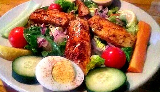 three slices of grilled chicken over a salad with dressing on the side
