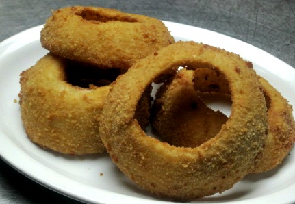 Onion rings on white dish.