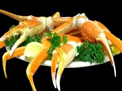 Crab claws plated with lemon wedge and garnished