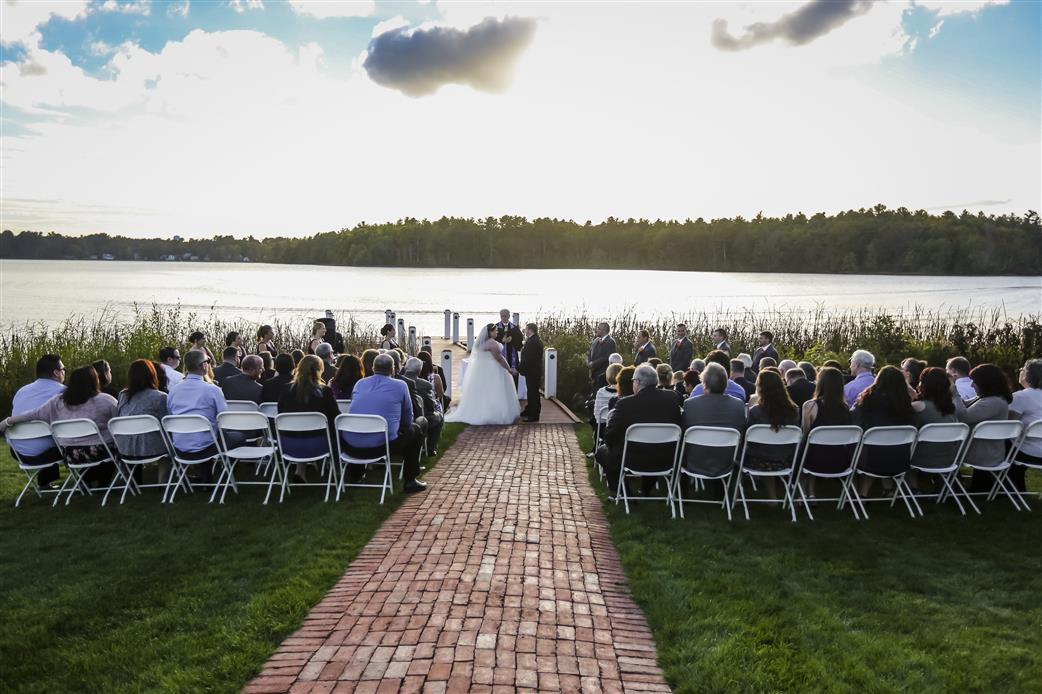 wedding ceremony taking place outdoors near a lake