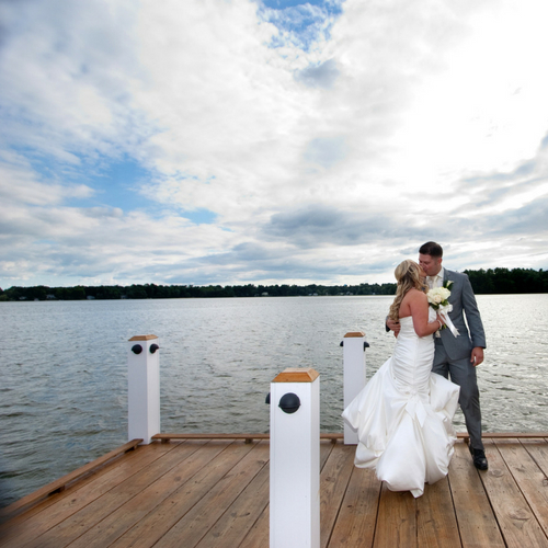 Bride and Groom  kissing on a dock near a lake