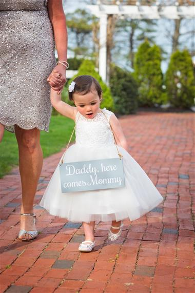 "Flowergirl holding a sign that says ""daddy, here comes mommy"""