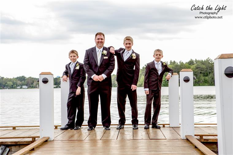 Groomsmen standing together on a dock smiling for the camera