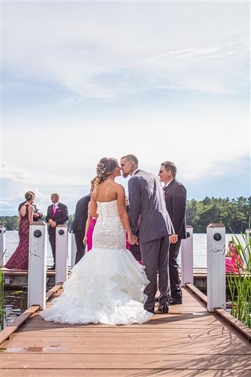 bride and groom kissing on a lake with the wedding party