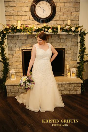 bride holding flowers near a fireplace