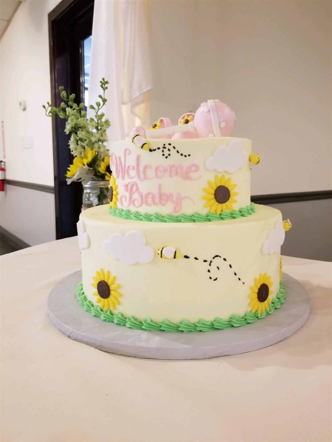 "Cake that says 'welcome baby"" with decorative flowers"