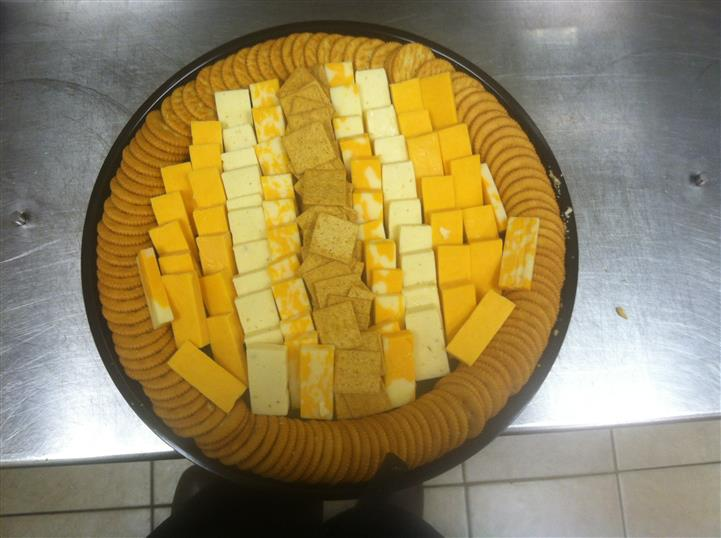 A plate with a selection of pieces of cheese and crackers