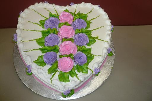 heart shaped cake with edible flowers in the middle of it