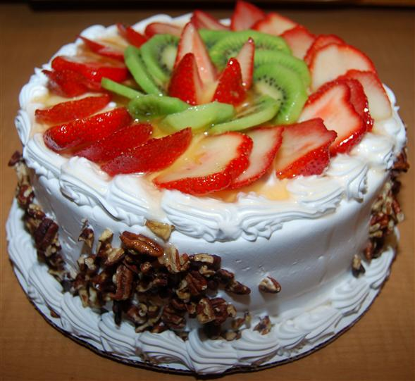 cake with icing topped with sliced fruit and chopped nuts on the side