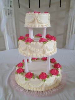three layer cake with vanilla icing and roses