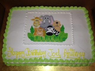 birthday cake printed with various animal faces in the middle