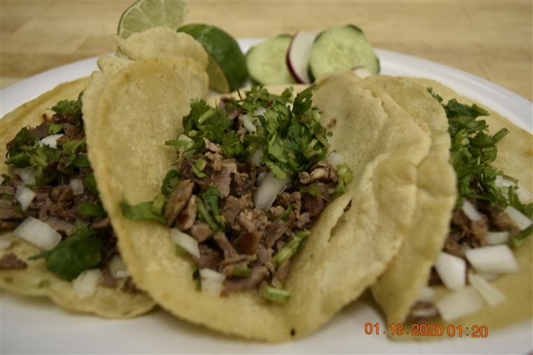 3 street tacos with ground beef, cilantro, and onions on corn tortillas served with lime