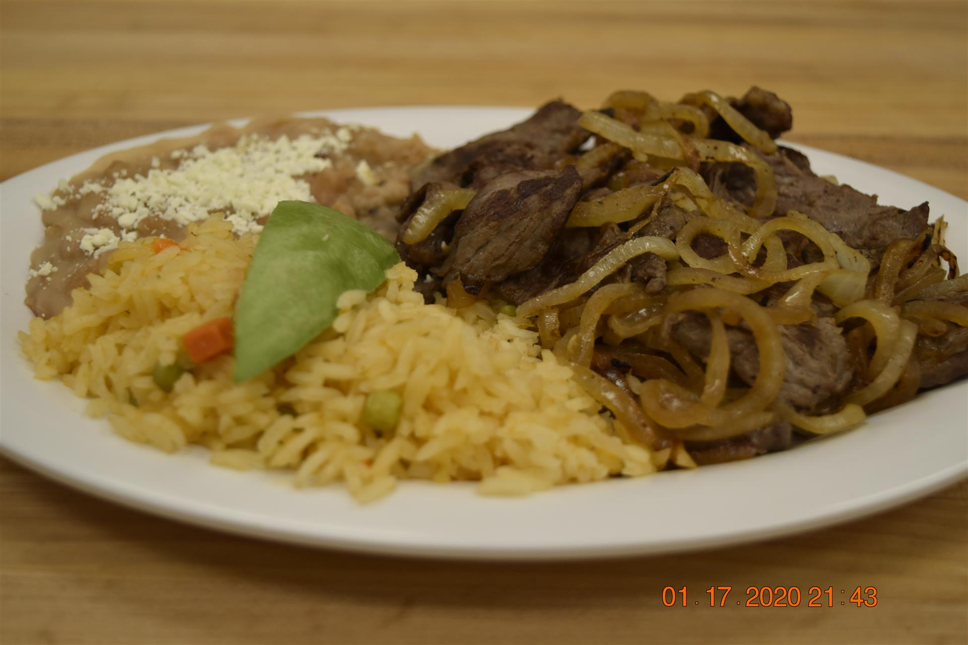 steak with onions, rice and beans