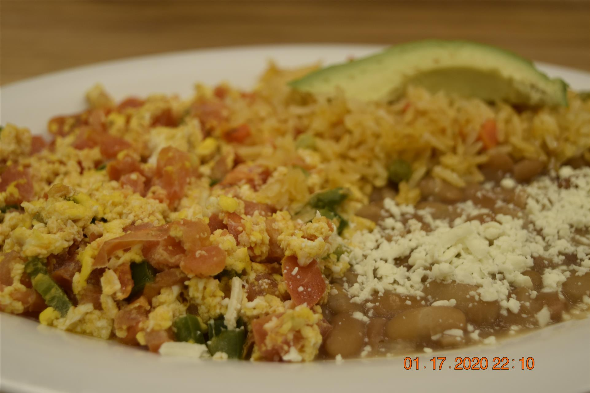 scrambled eggs with vegetables, and side of rice and beans