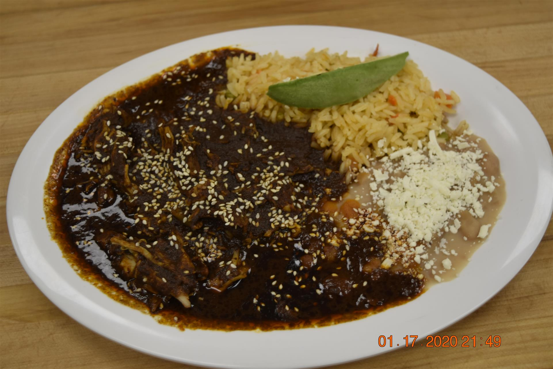 meat dish in a brown sesame sauce with side of rice and beans