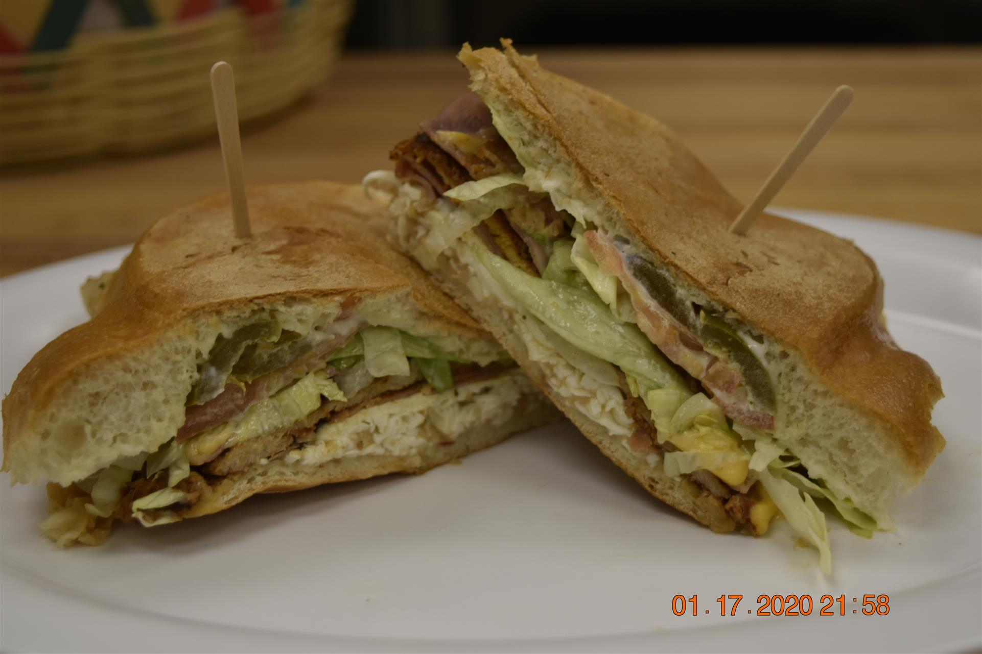 two halves of a deli sandwich with ham and lettuce