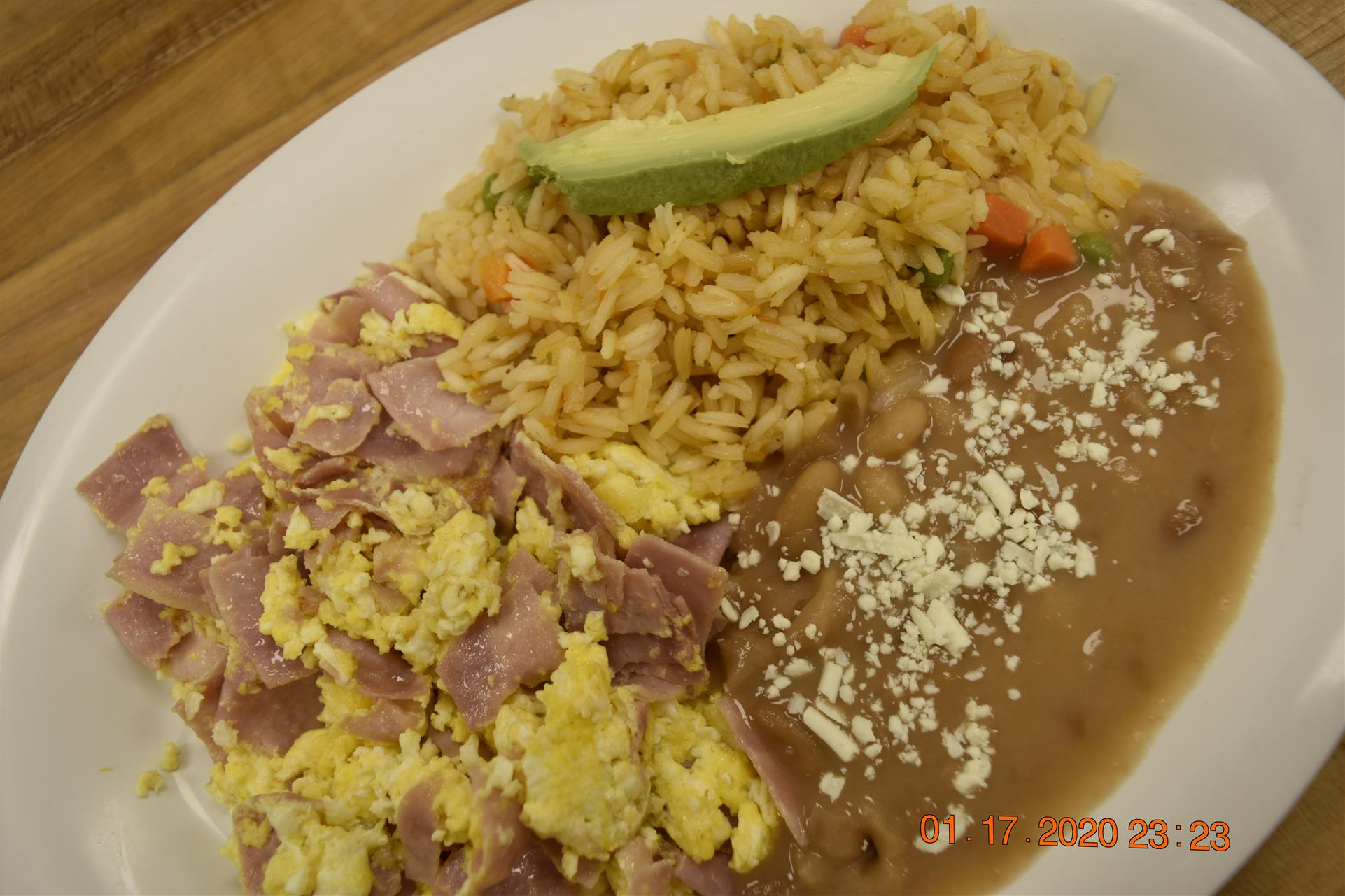 scrambled eggs and ham with side of rice and beans