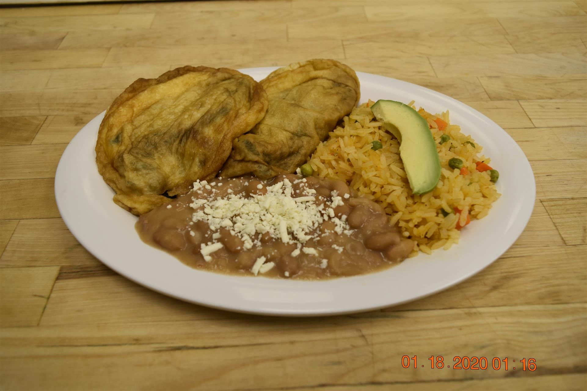 fried dish with side of rice and beans