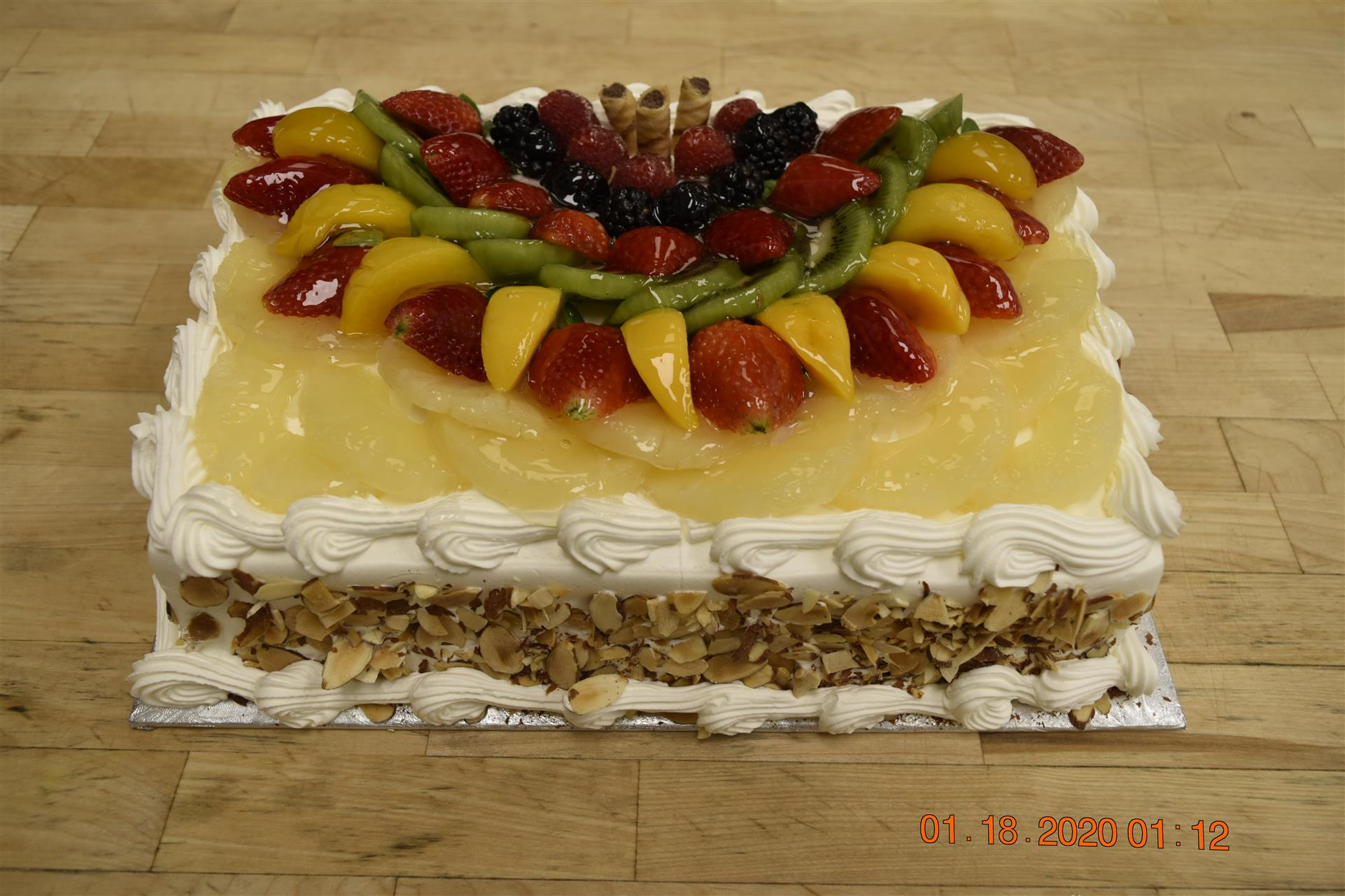 rectangular vanilla cake with nuts and various fruits
