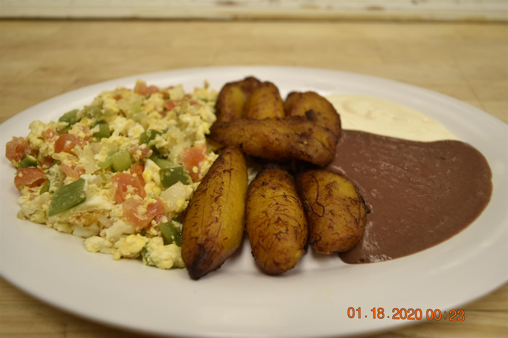 fried plantains with side of scrambled eggs and beans