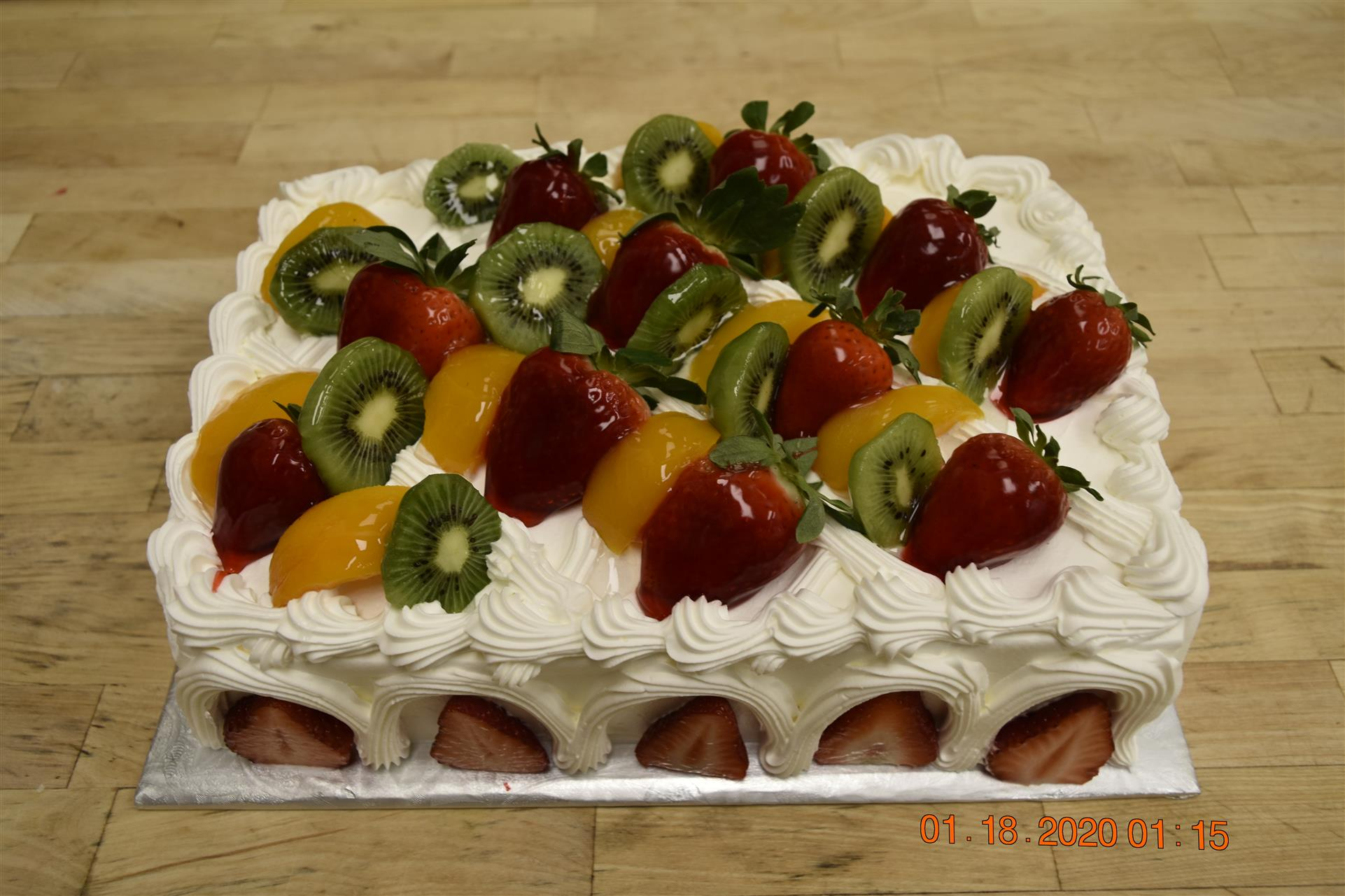 vanilla cake topped with strawberries, kiwis, and peaches