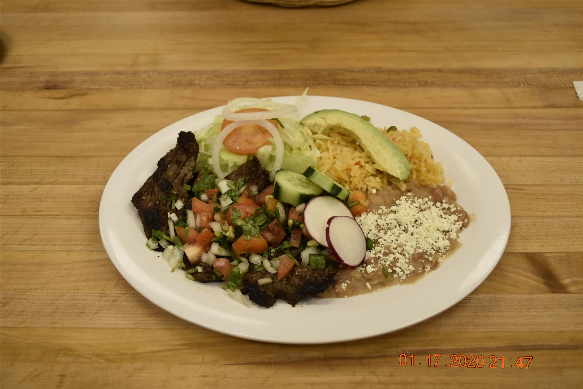 meat dish with side of rice, beans and salad