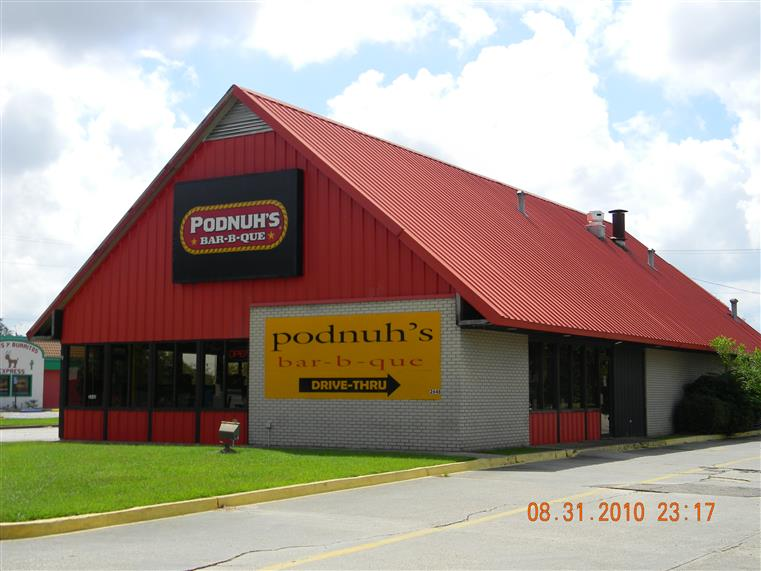 Front of Podnuh's building with peaked roof and sign on wall.