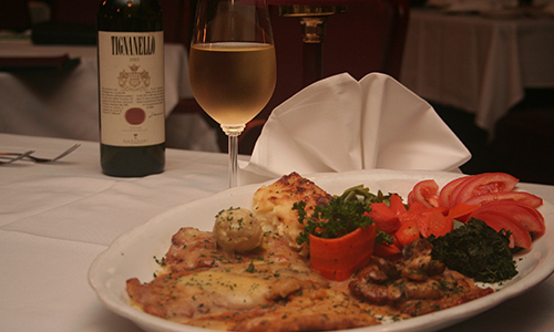 plate of appetizers with glass of wine and bottle of wine