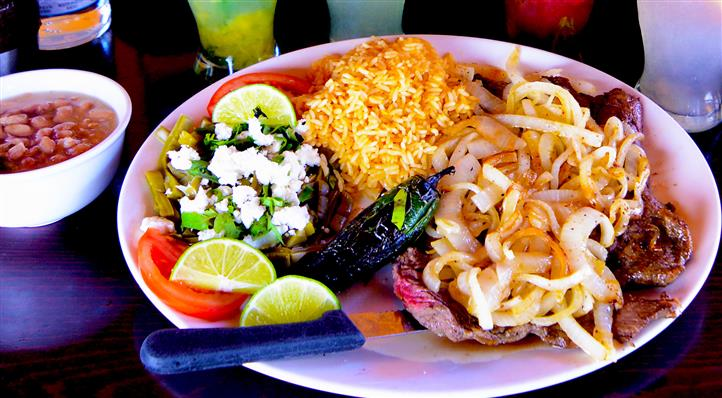 Grilled beef topped with sauteed onions, sauteed greens with shredded cheese, rice and a jalapeno