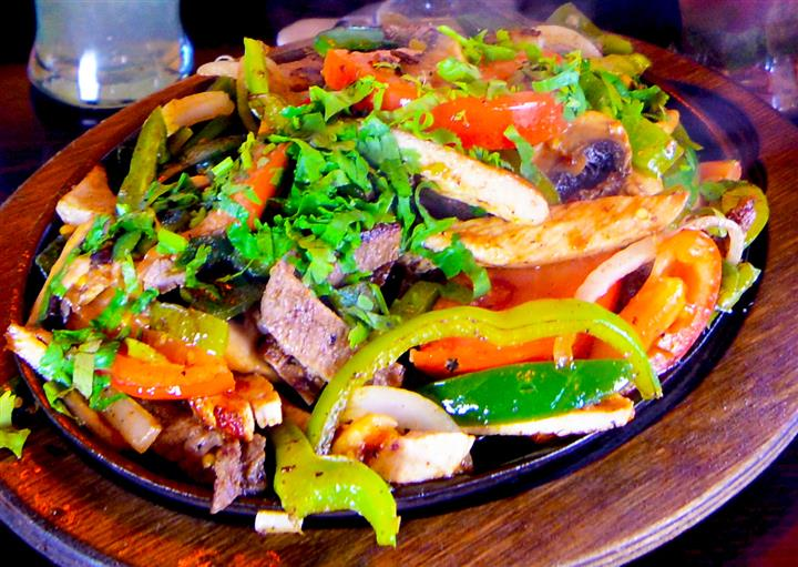 A platter of shredded beef served with red and green peppers, mushrooms, tortillas, tomatoes and other vegetables