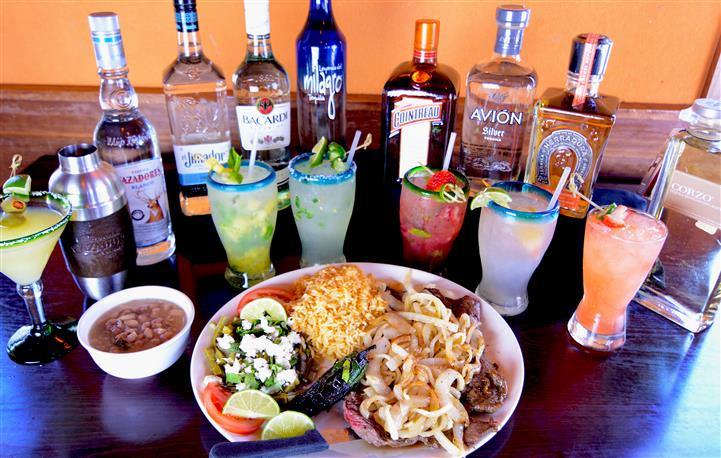 Grilled beef topped with sauteed onions, sauteed greens with shredded cheese and rice and a bowl of beans soup in front of bottles of drinks and fresh cocktails