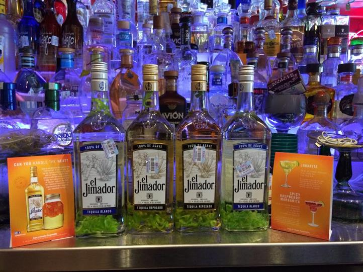 4 bottles of El Jimador in front of a bar with a great variety of bottles of drinks