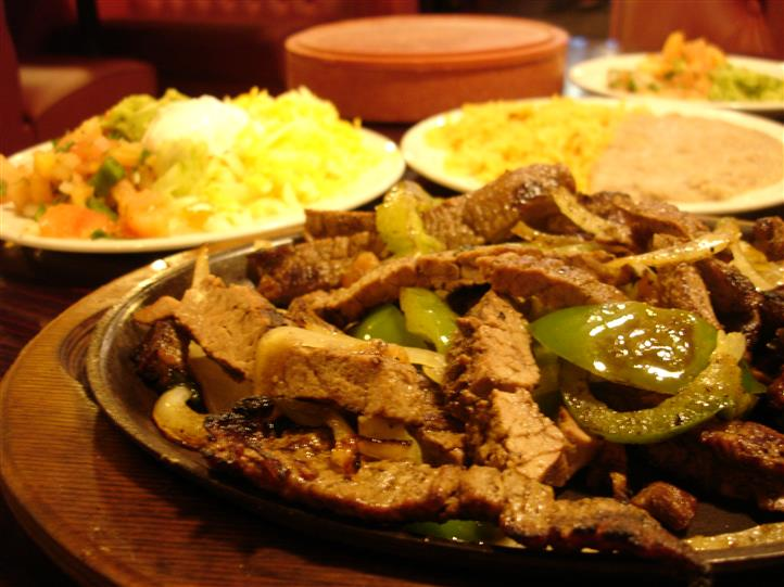 A platter of grilled beef served with green peppers