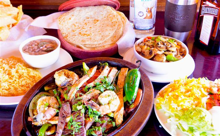 A variety of meat and shrimp served with vegetables, surrounded by 3 Mexican dishes, served with tortillas