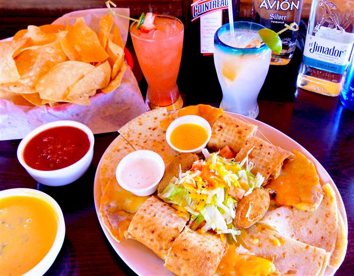 A Mexican dish served with tortilla chips chips and dips, with two cocktails