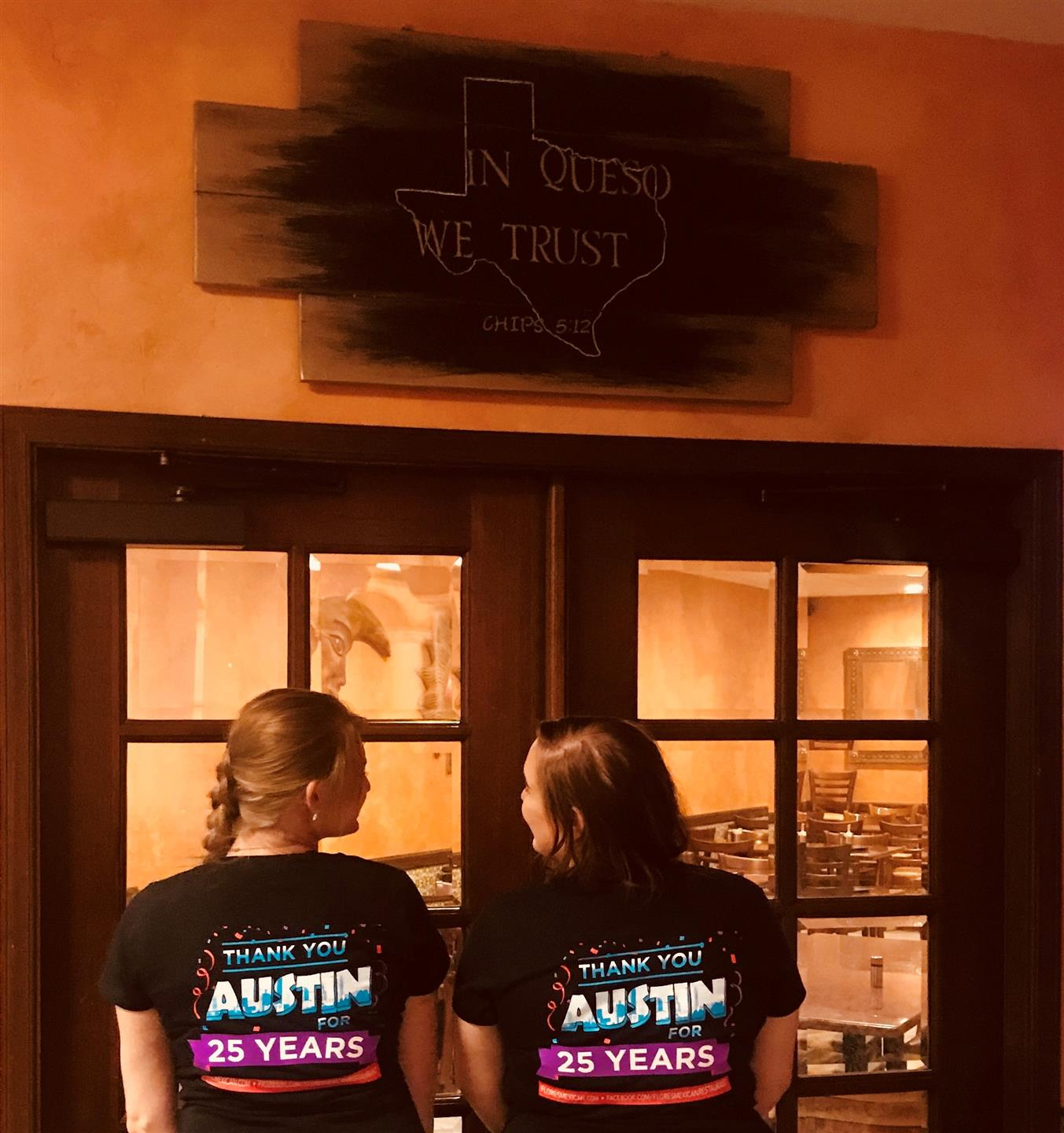 "two women in front of doorway with sign, with outline of texas that reads, ""In Queso We Trust"""